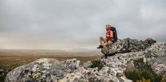 Hiker женщины сидя на холме ослабляя стоковая фотография