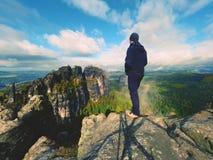 Hiker в черной стойке sportswear на пике утеса песчаника в империях утеса паркует и наблюдающ над туманом Стоковое Изображение RF