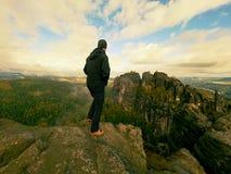 Hiker в черной стойке sportswear на пике утеса песчаника в империях утеса паркует и наблюдающ над туманом Стоковая Фотография