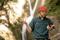 Hiker держит smartphone пробуя найти соединение в глубоком лесе с водопадами стоковая фотография rf
