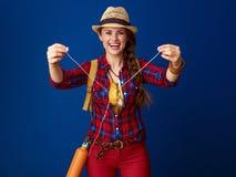 Hiker женщины изолированный на голубой предпосылке давая наушники Стоковое Фото