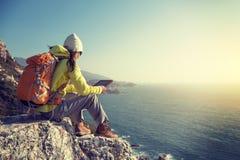 Hiker женщины используя цифровую таблетку сидит на скале взморья Стоковые Изображения RF