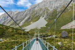 Hiker женщины идя на висячий мост Стоковая Фотография