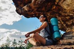 Hiker женщины наслаждается взглядом на скале горного пика захода солнца Стоковая Фотография RF