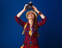 Hiker женщины на голубой предпосылке при камера DSLR принимая фото Стоковая Фотография RF