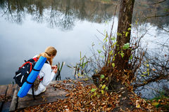Hiker женщины на деревянной платформе в реке осени Стоковые Изображения RF