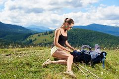 Hiker женщины на травянистом холме, нося рюкзаке, используя trekking ручки в горах стоковые фотографии rf