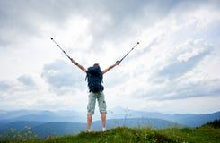 Hiker женщины на травянистом холме, нося рюкзаке, используя trekking ручки в горах стоковая фотография rf