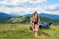 Hiker женщины на травянистом холме, нося рюкзаке, используя trekking ручки в горах стоковая фотография