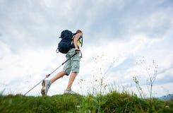 Hiker женщины на травянистом холме, нося рюкзаке, используя trekking ручки в горах стоковые фото