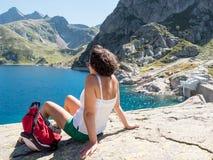 Hiker женщины отдыхает около озера горы Стоковая Фотография
