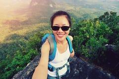 Hiker женщины принимая фото с мобильным телефоном на горный пик Стоковое Фото