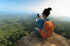 hiker женщины принимая фото с smartphone на скале горного пика Стоковая Фотография RF