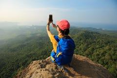 hiker женщины принимая фото с smartphone на скале горного пика Стоковое Фото