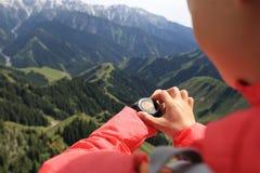Hiker женщины проверяя высотометр на вахте спорт на горном пике Стоковые Изображения