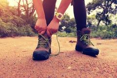 Hiker женщины связывая шнурок на следе леса Стоковые Фото