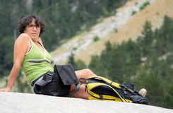 Hiker женщины сидя на утесе Стоковое Фото