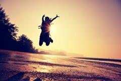 Hiker женщины скача на пляж восхода солнца Стоковое Фото