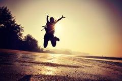 Hiker женщины скача на пляж восхода солнца Стоковые Изображения RF