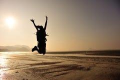 Hiker женщины скача на пляж восхода солнца Стоковое фото RF