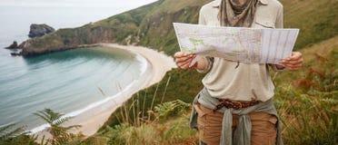 Hiker женщины смотря карту перед ландшафтом вида на океан Стоковые Изображения