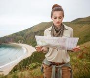 Hiker женщины смотря карту перед ландшафтом вида на океан Стоковая Фотография
