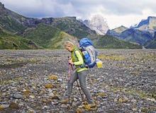 Hiker женщины с рюкзаком идя вверх по следу с красивым ландшафтом взгляда горных пиков Стоковая Фотография