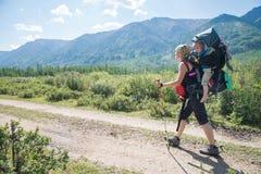 Hiker женщины trekking в горах с ребенком в рюкзаке Мать при ребёнок путешествуя в дне лета солнечном Стоковые Изображения