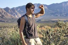 Hiker защищает глаза от солнца в пустыне Стоковое Фото