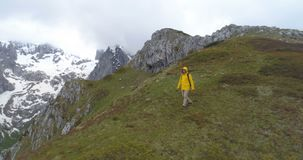 Hiker идет на холм на фоне снег-покрытых гор видеоматериал