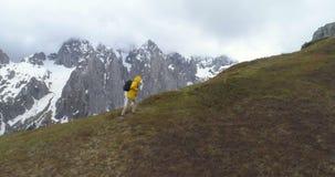 Hiker идет на холм на фоне снег-покрытых гор акции видеоматериалы