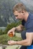 Hiker льет воду от бутылки с водой на его руках Стоковое Изображение