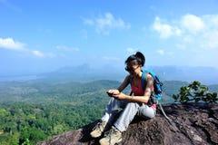 Hiker молодой женщины используя smartphone Стоковые Фото