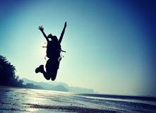 Hiker молодой женщины скача на пляж восхода солнца Стоковые Изображения RF