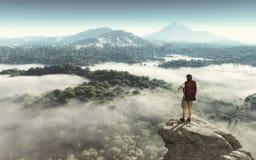Hiker на верхней части горы смотря ландшафт Стоковая Фотография RF