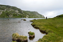 Hiker озером горы в пасмурном дне Стоковые Изображения RF
