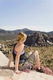 Hiker отдыхая на скале Стоковое Изображение