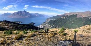 Hiker принимая фото как показано его тенью пока на бдительности над шикарным городком Queenstown и озера Wakatipu стоковое изображение