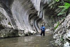 Hiker пропуская через воду в ущелье Стоковое Изображение
