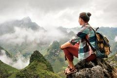 Hiker сидя na górze горы наслаждаясь на взгляде туманного держателя стоковое изображение