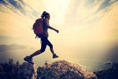 Hiker скача на утес горного пика взморья Стоковая Фотография