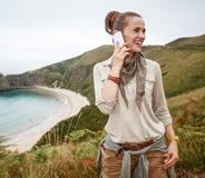 Hiker смотря в сторону и используя мобильный телефон перед океаном Стоковые Фотографии RF