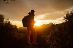 Hiker стоит на скале над восходом солнца Стоковые Фотографии RF