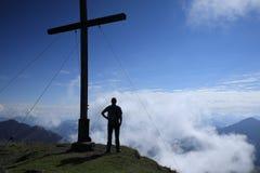 Hiker стоит около креста Стоковое Фото