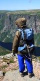Hiker стоя на ветреном крае скалы Стоковое Изображение RF