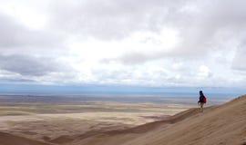 Hiker стоя на пике песчанных дюн стоковое изображение rf