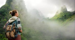 Hiker с рюкзаком в горах наслаждаясь на взгляде туманного держателя стоковая фотография rf