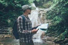 Hiker с рюкзаком готовит водопад и смотрит праздники карты и концепцию туризма стоковые изображения rf