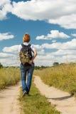 Hiker с рюкзаком идя на сельскую дорогу Стоковые Изображения RF