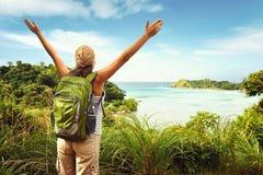 Hiker с рюкзаком наслаждаясь видом на море от верхней части горы Стоковая Фотография RF